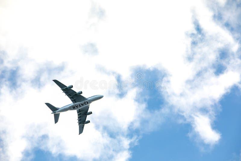 卡塔尔空中客车飞机飞行在城市,蓝色和多云天空 卡塔尔航空是卡塔尔的国营航空公司,根据在多哈 免版税库存图片