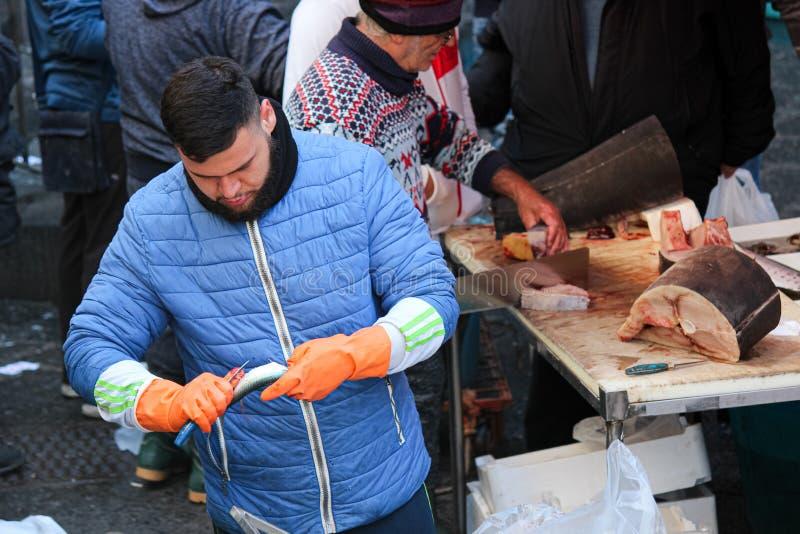 卡塔尼亚,意大利- 2019年4月10日:在著名西西里人的鱼市上的幼小渔夫结垢和毁坏鱼 拉出獐鹿 免版税库存照片