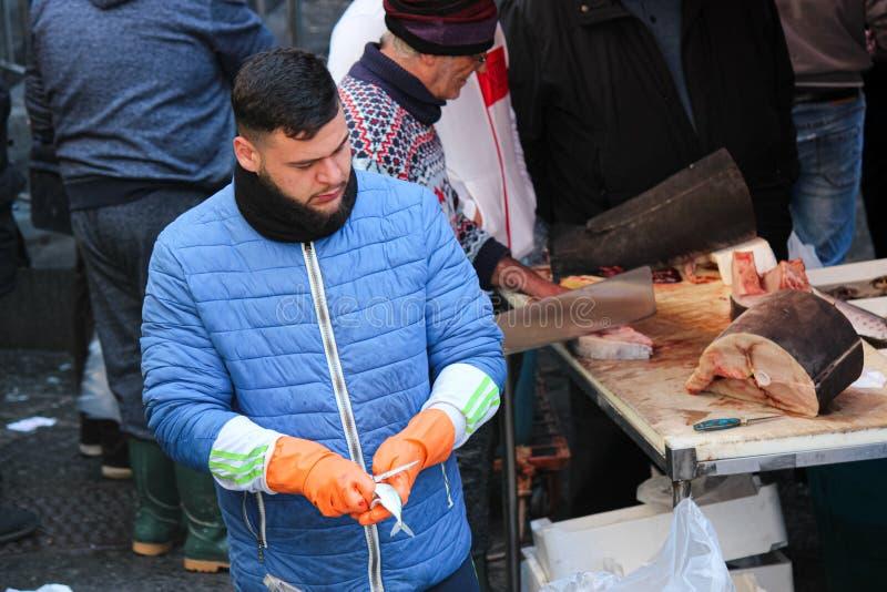 卡塔尼亚,意大利- 2019年4月10日:拔出獐鹿和胆量的鱼贩子在一条小鱼外面 毁坏是必要的步 库存图片