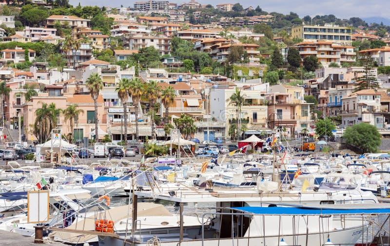 卡塔尼亚,西西里岛,意大利–威严08日2018年:Acitrezza口岸看法与渔夫小船的在独眼巨人海岛旁边,美好的都市风景 图库摄影