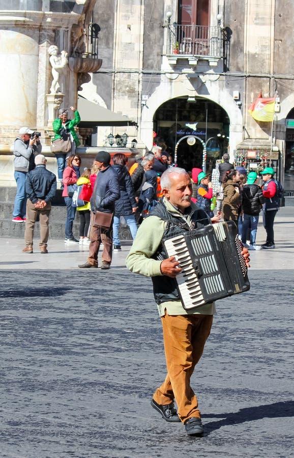 卡塔尼亚,西西里岛,意大利- 2019年4月10日:演奏在广场中央寺院正方形的更老的灰色人卖艺人手风琴在老镇 免版税库存图片