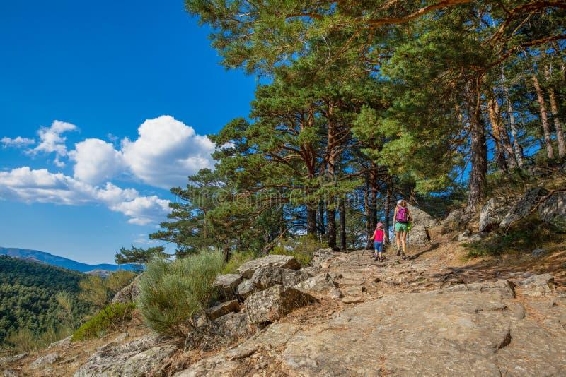 卡嫩西亚山风景与步行在一串足迹的妇女和女孩的在森林里 免版税库存图片