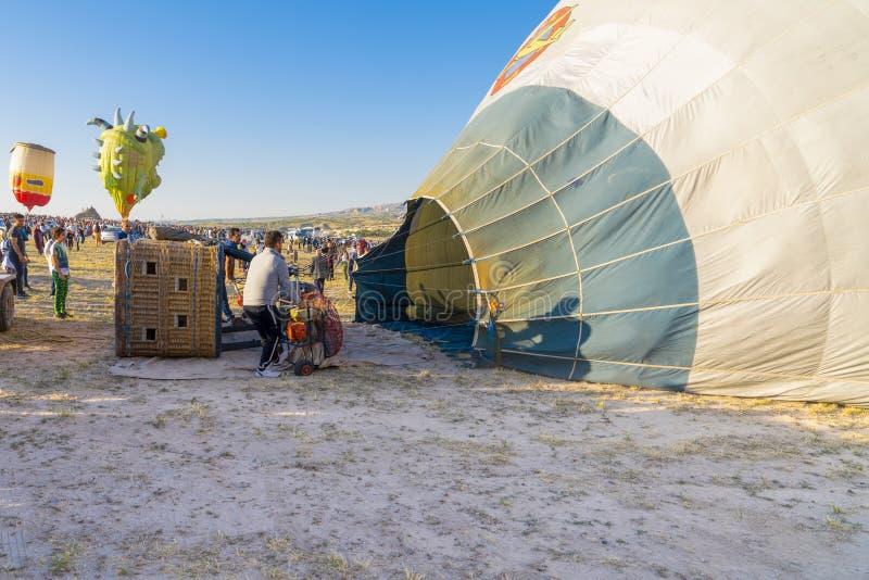 卡帕多细亚/土耳其- 2019年7月07日:在日落的乘员组热空气气球为飞行做准备 汇编和填装气球 库存照片