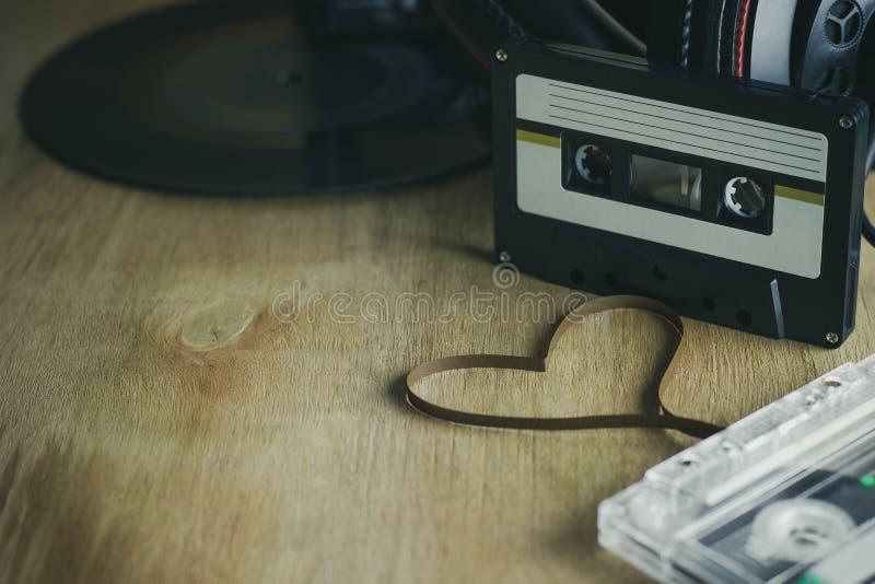 卡式磁带心形的磁带和耳机有唱片盛肉盘的 免版税库存图片