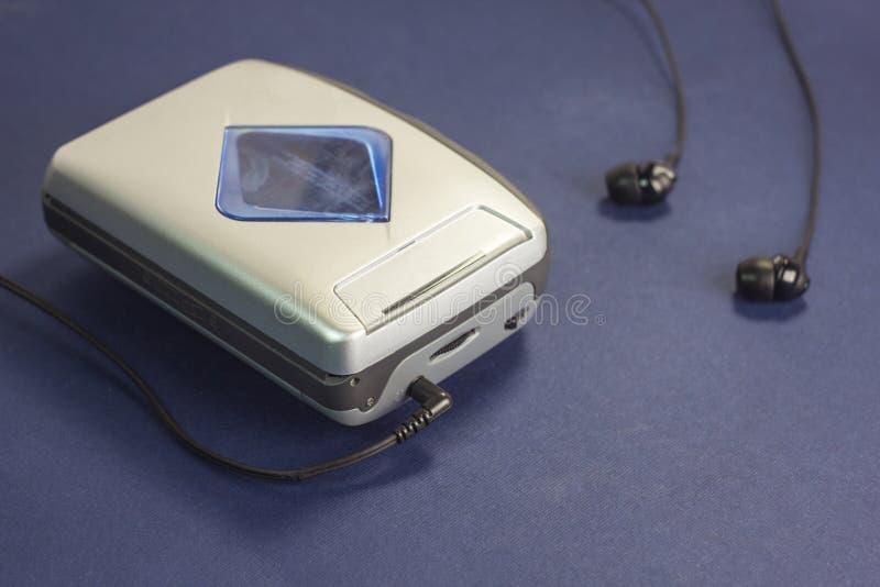 卡式磁带音频球员和耳机在蓝色背景娱乐 免版税库存图片