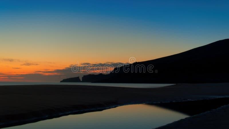 卡拉市Mesquida,日出,海滩,地中海,小山,岩石,在水,与云彩的天空蔚蓝,马略卡的金黄太阳反射, 库存照片