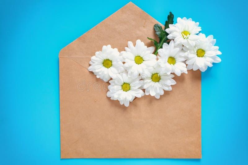 卡拉服特信封和白色菊花在蓝色背景 复制空间和室署名的 美妙9心情多彩多姿的照片被设置的春天的郁金香 库存图片