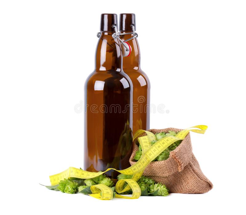 卡拉服特啤酒的玻璃瓶与蛇麻草新绿色分支和黄色测量在白色背景录音,隔绝 免版税库存图片