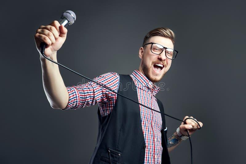 卡拉OK演唱人唱歌曲到话筒,有胡子的歌手在灰色背景 拿着话筒的玻璃的滑稽的人 免版税图库摄影