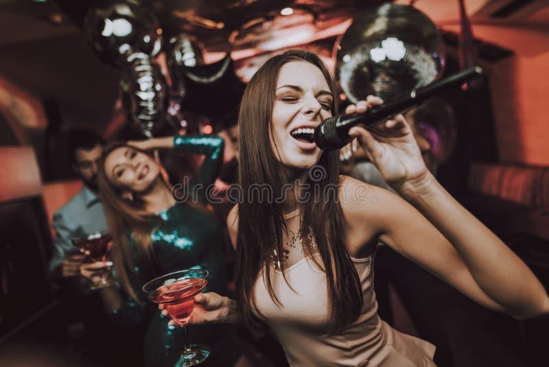 卡拉OK演唱俱乐部 唱歌并且喝 美丽的女孩 库存图片