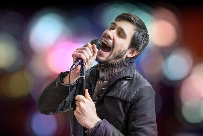 卡拉OK演唱概念 年轻人举行话筒和唱在被弄脏的背景的一首歌曲 免版税库存照片