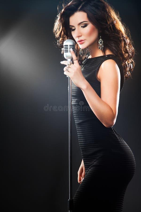 卡拉OK演唱的美丽的唱歌的女孩 有减速火箭的话筒的秀丽妇女 库存图片