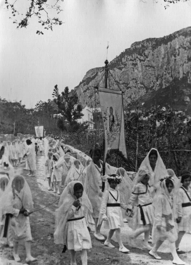 卡普里,意大利,1929年-在圣科斯坦佐的庆祝期间,少女在白色礼服,海岛的赞助人游行 库存照片