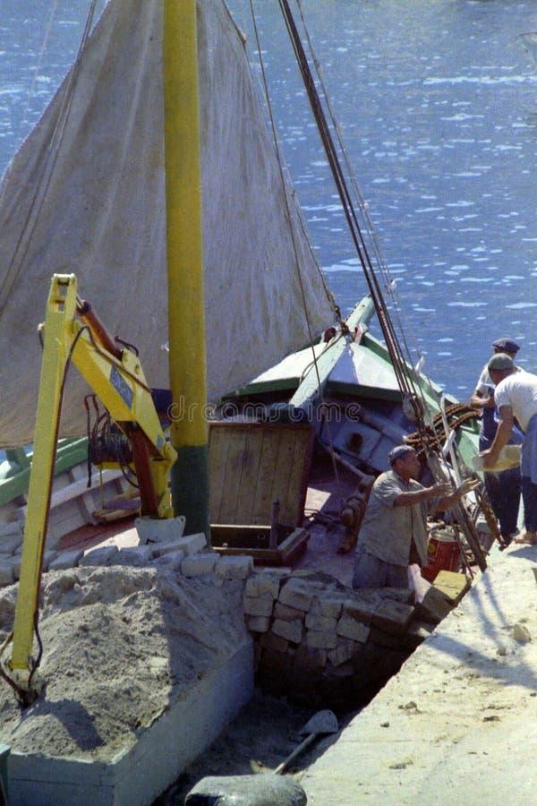 卡普里,意大利,1974年-工作者卸载砖和建筑材料从一只货船在港口船坞 免版税库存图片