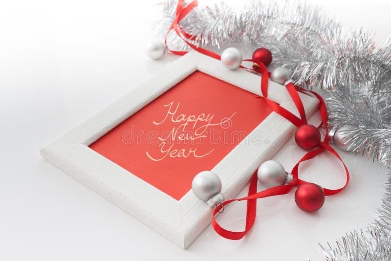 贺卡模板由白色框架和红牌制成与红色丝带,银和红色球和银色闪亮金属片 免版税图库摄影