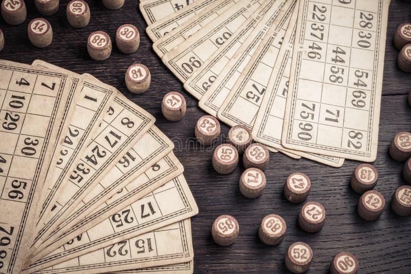 卡片和乐透纸牌小桶在木背景在葡萄酒样式 免版税库存照片