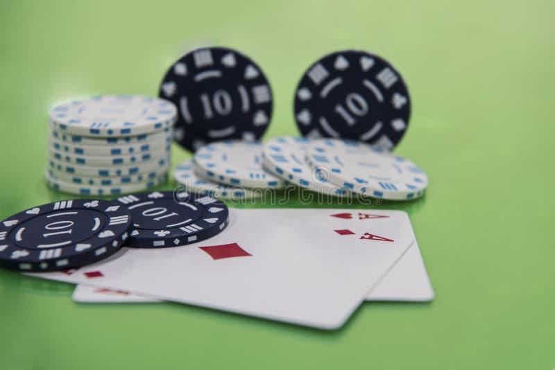 卡片和芯片在绿色和黄色赌博娱乐场桌上 抽象赌博娱乐场赌博的照片 免版税库存照片