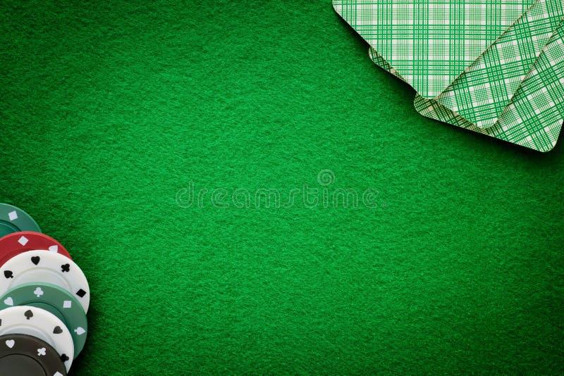 卡片和芯片在绿色毛毡赌博娱乐场桌上 抽象背景 库存图片