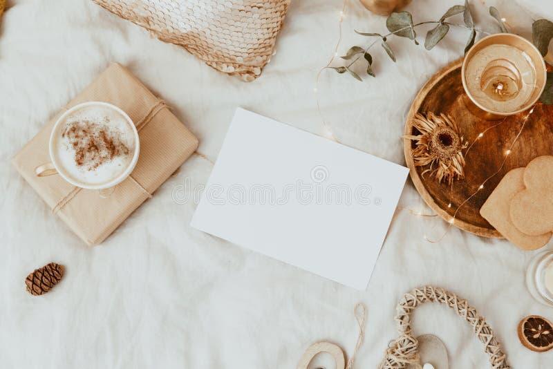 卡片的嘲笑 与咖啡杯、曲奇饼和金装饰的背景在床上 库存照片