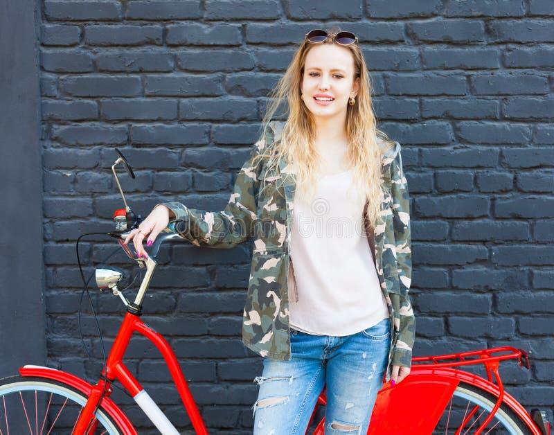 卡莫公共事业大衣 摆在与在街道上的一辆时髦葡萄酒红色自行车的时兴的成套装备的一个美丽的女孩 库存图片