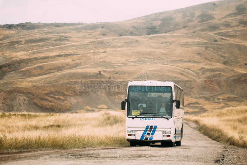 卡赫季州地区,乔治亚-有游人乘驾的公共汽车在秋天风景背景的Gareji沙漠在Sagarejo 免版税库存图片