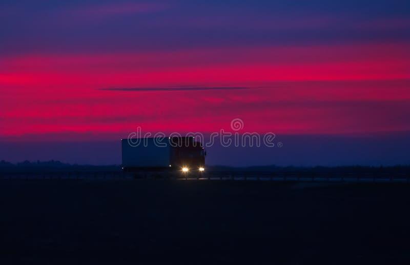 卡车在日落的高速公路去 免版税库存照片