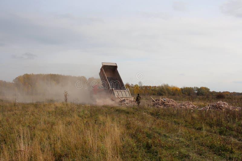 卡车在领域倾销从建筑废料身体的残骸违犯法律危害环境人观看 库存图片