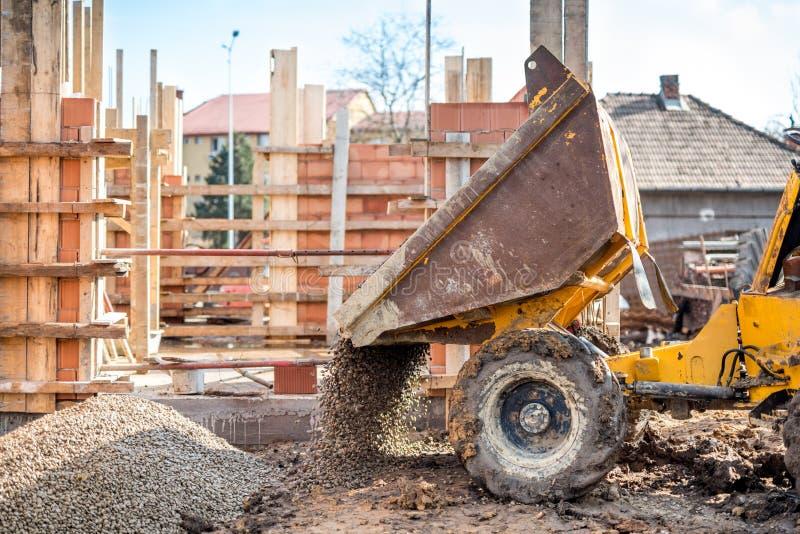 卡车装载者挖掘的石渣和建筑聚集体 有倾销者卡车和材料的建造场所 库存照片