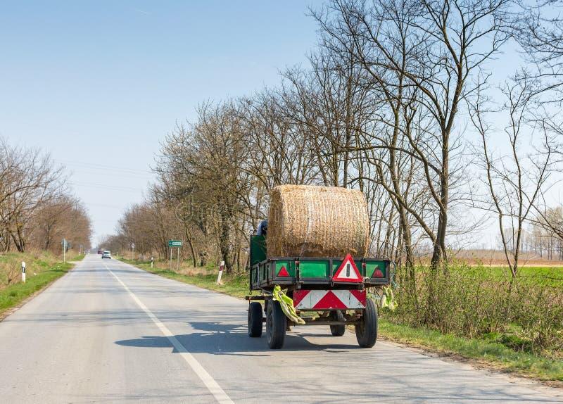 卡车运载沿柏油路的一干草卷 库存照片