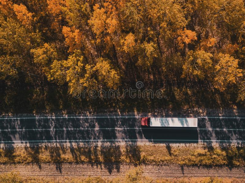 卡车鸟瞰图在路的通过森林在秋天 库存照片