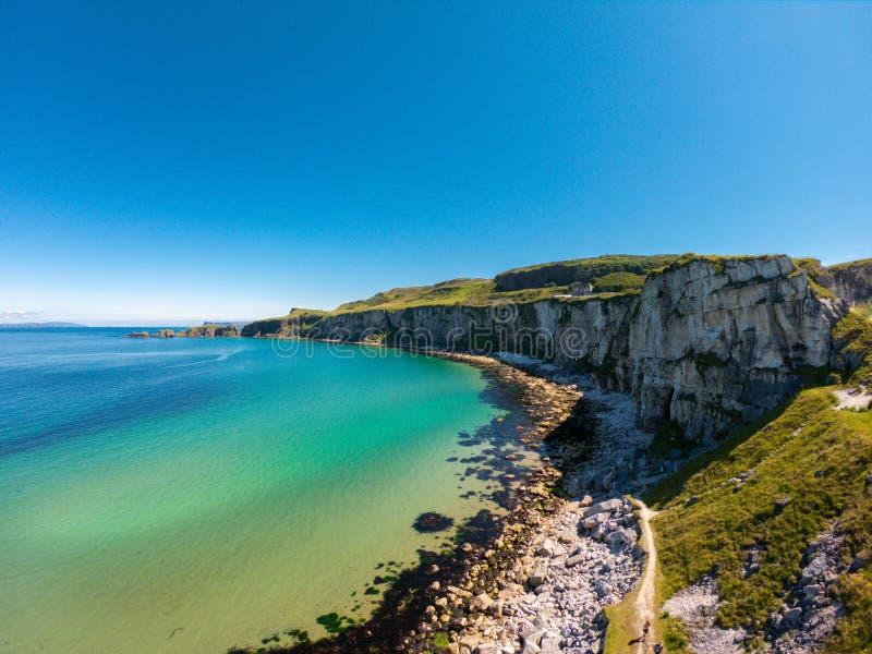 卡里克一座Rede索桥在Ballintoy北爱尔兰 在峭壁和绿松石大西洋水的鸟瞰图 图库摄影