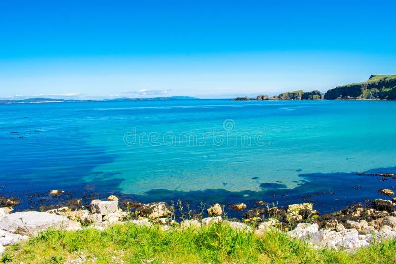 卡里克一座Rede索桥在Ballintoy,北爱尔兰 在大西洋,清楚的蓝色和绿色wa海岸的美好的风景  库存图片