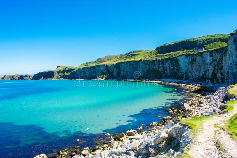 卡里克一座Rede索桥在Ballintoy,北爱尔兰 在大西洋,清楚的蓝色和绿色wa海岸的美好的风景  图库摄影