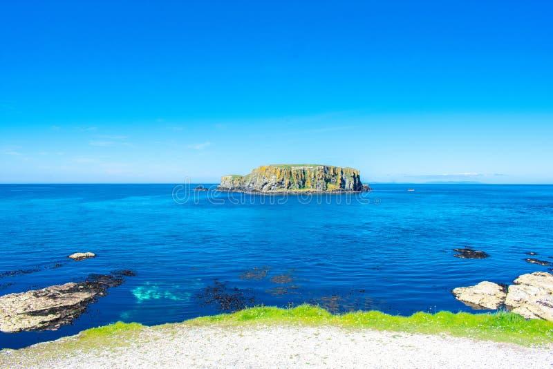 卡里克一座Rede索桥在Ballintoy,北爱尔兰 在大西洋,清楚的蓝色和绿色wa海岸的美好的风景  库存照片