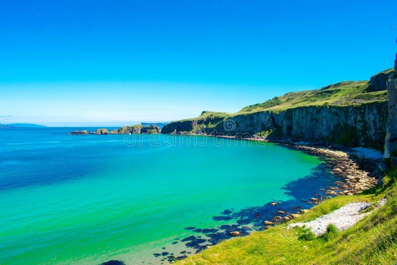 卡里克一座Rede索桥在Ballintoy,北爱尔兰 在大西洋,清楚的蓝色和绿色wa海岸的美好的风景  免版税图库摄影