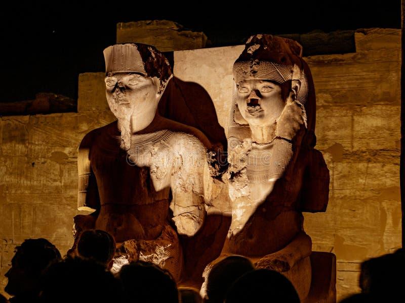 卢克索神庙的女王/王后国王Tutankhamun和他的在埃及由参观卢克索神庙的游人围拢了在晚上 免版税库存图片