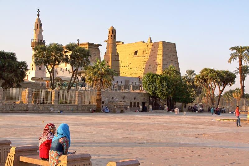 卢克索,埃及- 2011年11月4日:坐在卢克索神庙前面的两个年轻埃及女孩 免版税库存图片