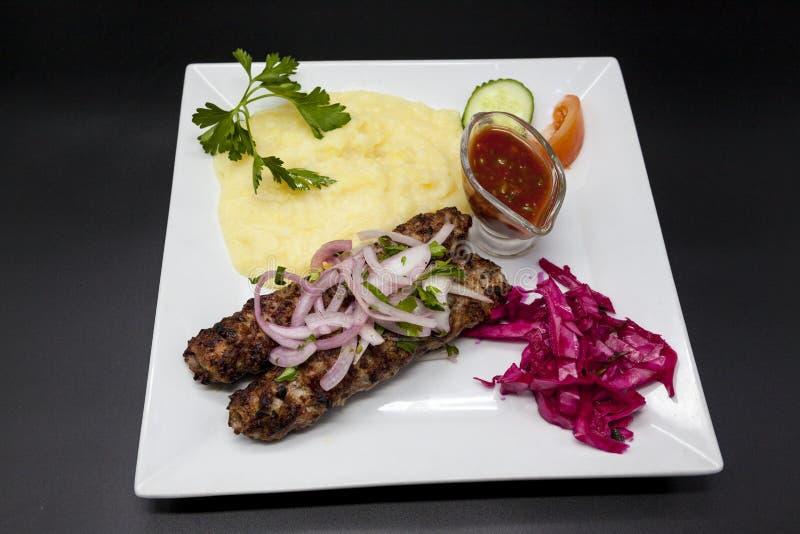 卢拉kebab Kebab 传统东方盘,烤肉烤肉串 羊羔,葱,圆白菜,捣碎了在pla的土豆辣西红柿酱 免版税库存图片