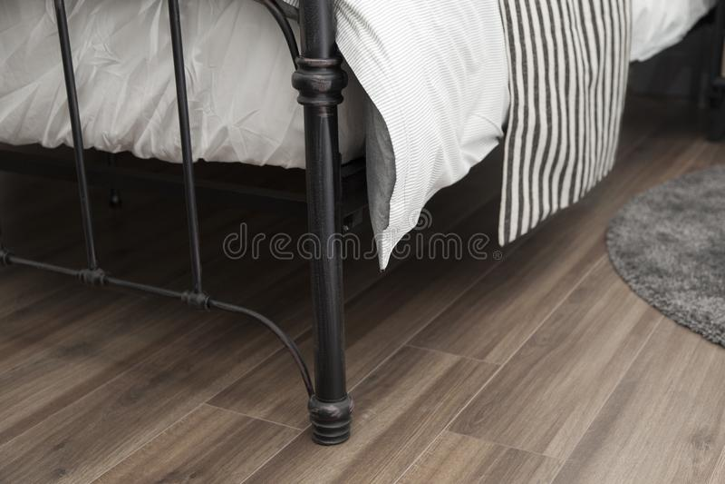 卧具与白色舒适的毯子和床垫的铁框架 免版税库存照片