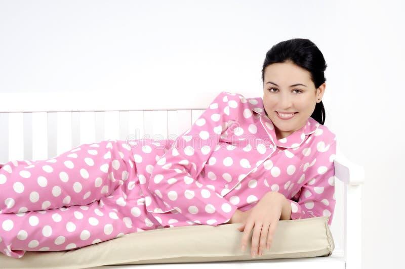 卧室位于的微笑的妇女年轻人 免版税库存照片
