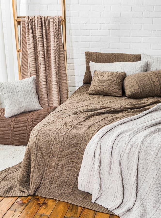 卧室床枕头毯子格子花呢披肩灰棕色 库存照片
