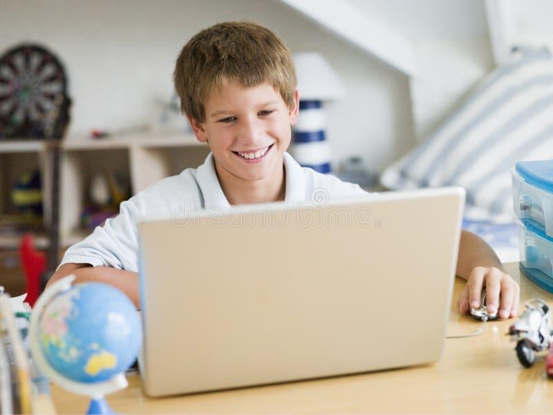 卧室男孩他的使用年轻人的膝上型计算机 库存照片