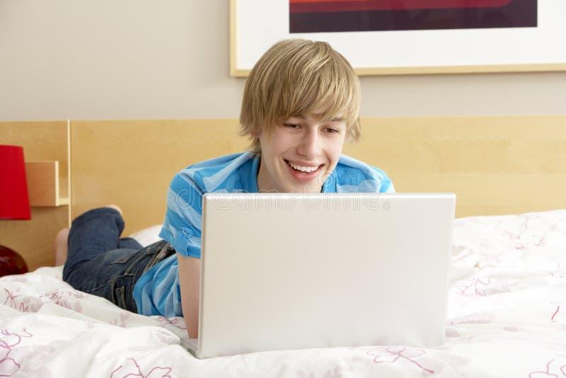 卧室男孩膝上型计算机少年使用 免版税库存图片