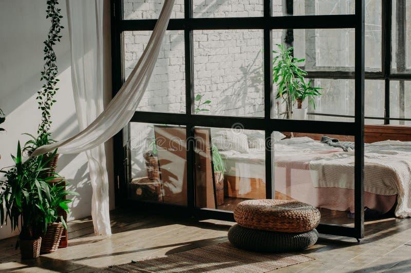 卧室顶楼内部 床、枕头、绿色植物和墙壁有白色砖的 免版税库存图片