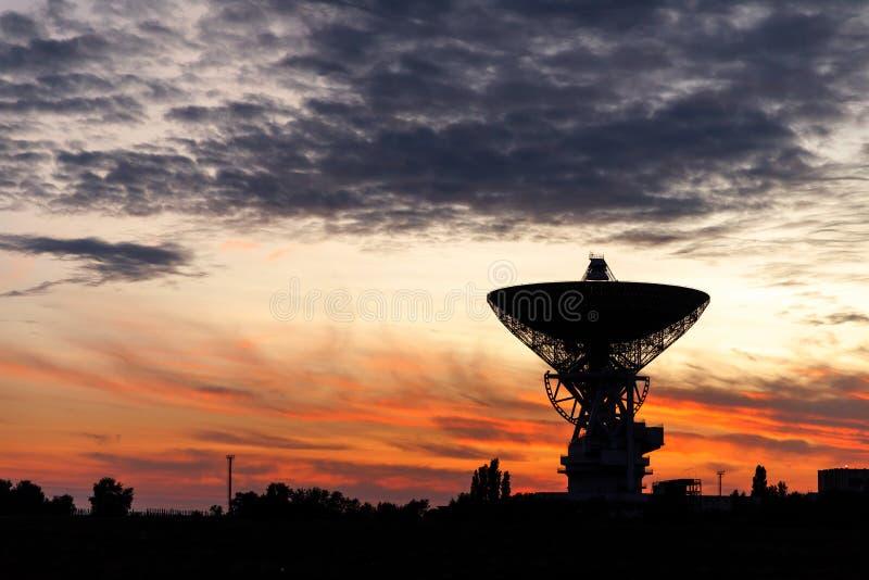 卫星盘的巨大的白色无线电望远镜反对天空的在日落期间 库存图片