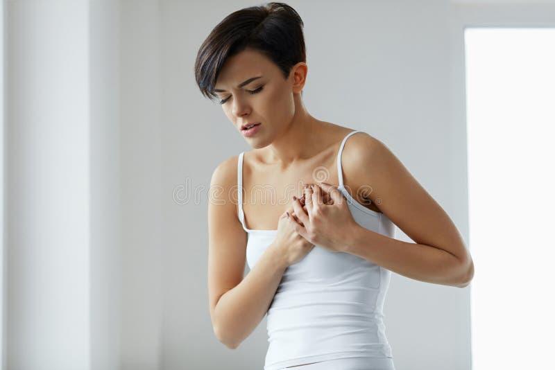 卫生问题 感觉在胸口的美丽的妇女强的痛苦 库存照片