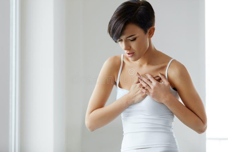 卫生问题 感觉在胸口的美丽的妇女强的痛苦 库存图片