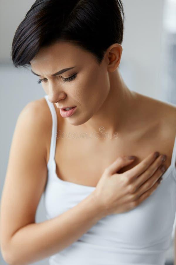 卫生问题 感觉在胸口的美丽的妇女强的痛苦 免版税库存照片