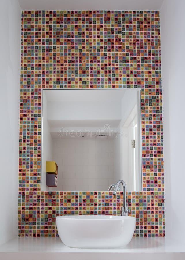 卫生间与五颜六色的玻璃锦砖和镜子插页的面盆到瓦片里 免版税库存图片