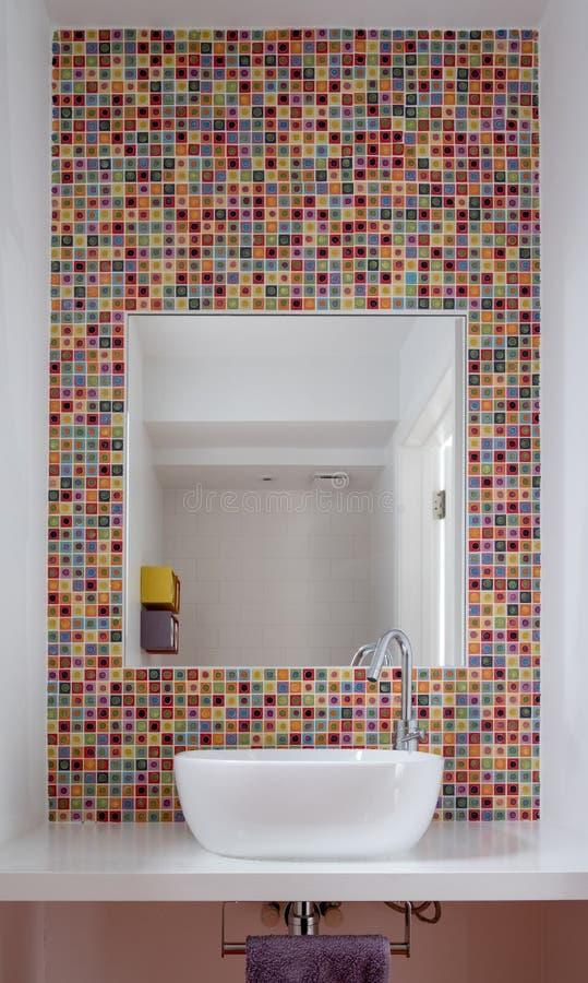 卫生间与五颜六色的玻璃锦砖和镜子插页的面盆到瓦片里 库存照片